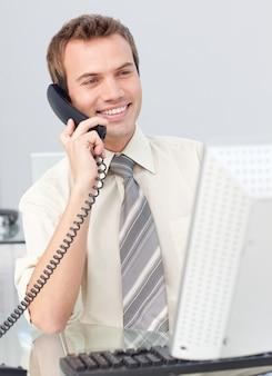 Geschäftsmann, der am telefon im büro spricht und mit einem computer arbeitet