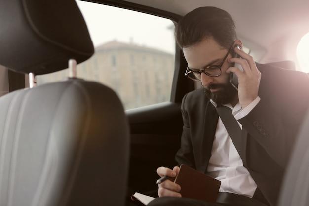 Geschäftsmann, der am telefon in einem auto spricht