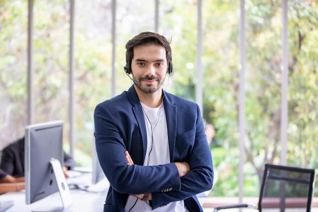 Geschäftsmann, der am telefon mit kopfhörer im büro spricht