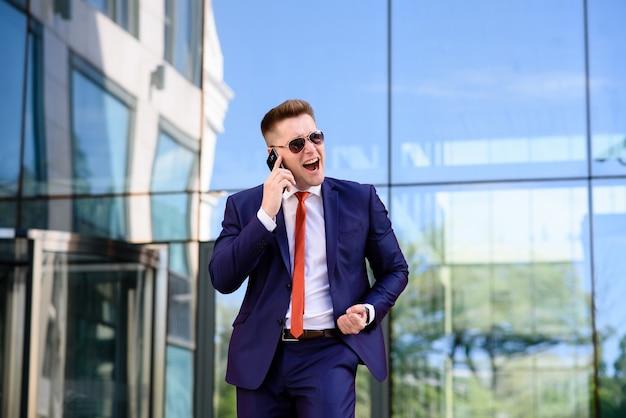 Geschäftsmann, der am telefon spricht und lächelt.