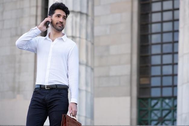 Geschäftsmann, der am telefon spricht, während er draußen auf treppen steht. geschäftskonzept.