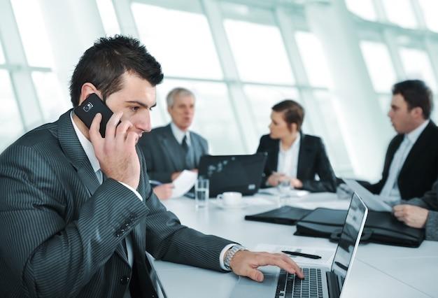 Geschäftsmann, der am telefon während in einer sitzung spricht