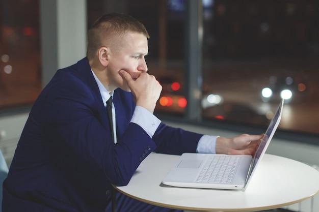 Geschäftsmann, der am tisch mit laptop nachts im büro arbeitet. außerhalb des fensters leuchten mehrfarbige lichter
