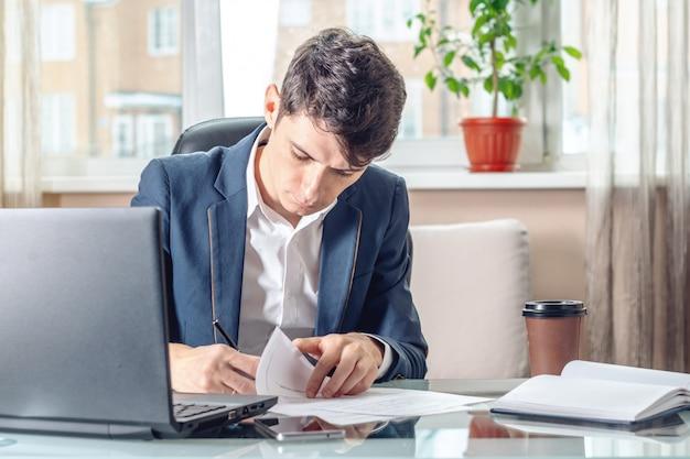 Geschäftsmann, der am tisch unterzeichnet dokumente im büro sitzt