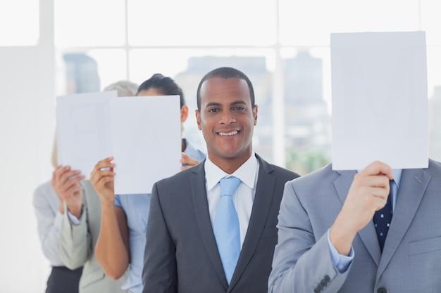 Geschäftsmann, der an der kamera mit den kollegen umfassen gesichter lächelt