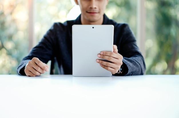 Geschäftsmann, der an digital-tablet im büro arbeitet. am schreibtisch sitzen.