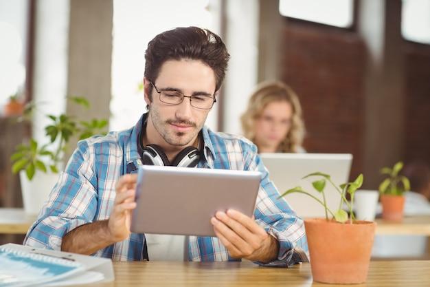 Geschäftsmann, der an digitaler tablette im hellen büro arbeitet