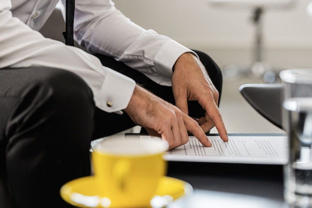 Geschäftsmann, der an einem büro-kaffeetisch sitzt, der ein dokument korrektur liest