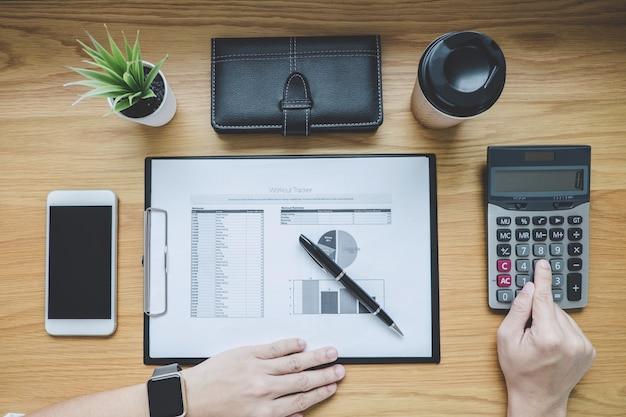 Geschäftsmann, der an einem diagrammdokumentfinanzbericht und analyseberechnungskosten mit taschenrechner am schreibtisch arbeitet