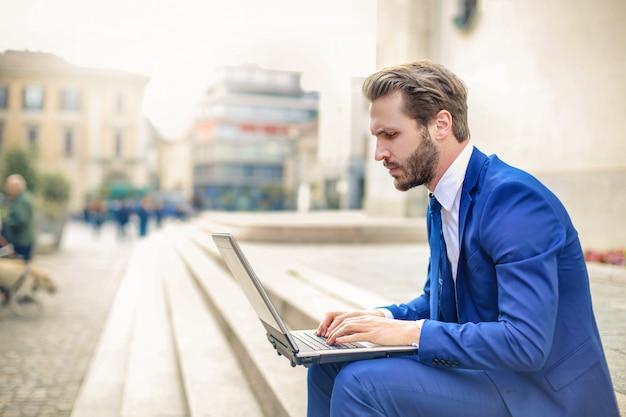Geschäftsmann, der an einem laptop im freien arbeitet