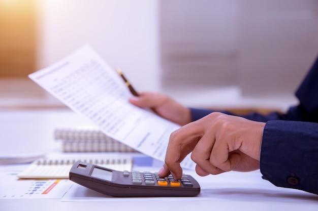 Geschäftsmann, der an einem schreibtisch mit einem taschenrechner arbeitet, um die zahlen zu berechnen.