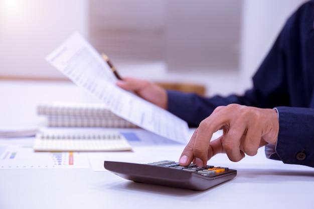 Geschäftsmann, der an einem schreibtisch mit einem taschenrechner arbeitet, um die zahlfinanzierung zu berechnen.