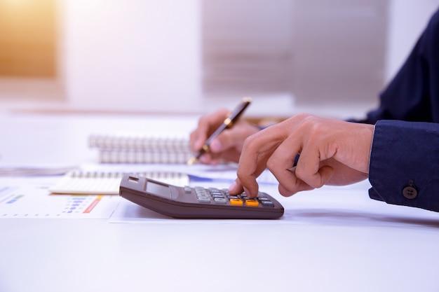 Geschäftsmann, der an einem schreibtisch mit einem taschenrechner zum calculat arbeitet.