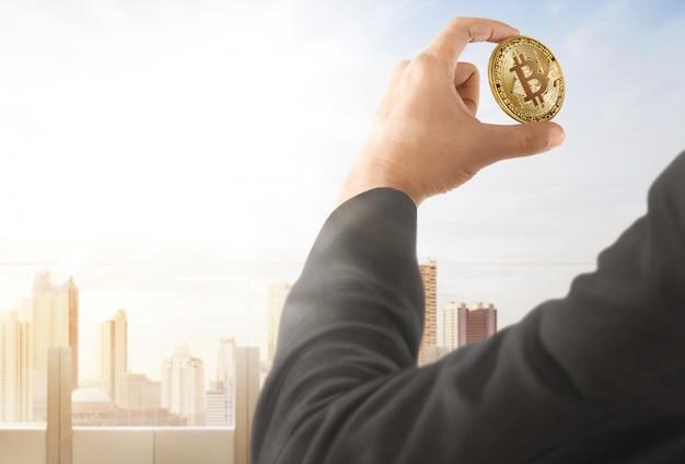 Geschäftsmann, der an hand bitcoin hält