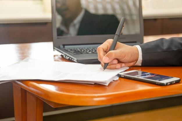 Geschäftsmann, der an laptop arbeitet und auf papiernotizbuch schreibt.
