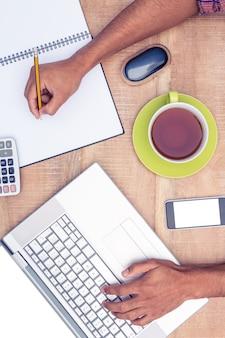 Geschäftsmann, der an laptop beim schreiben auf buch am schreibtisch im büro arbeitet