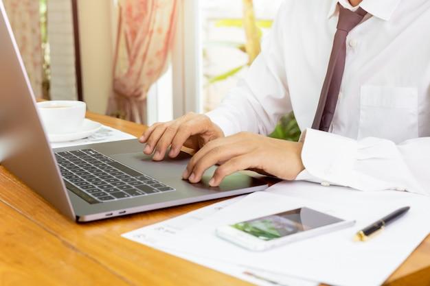 Geschäftsmann, der an laptop mit schreibarbeit auf tabelle arbeitet