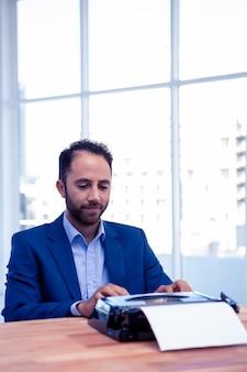 Geschäftsmann, der an schreibmaschine beim sitzen am schreibtisch im hellen kreativen büro arbeitet