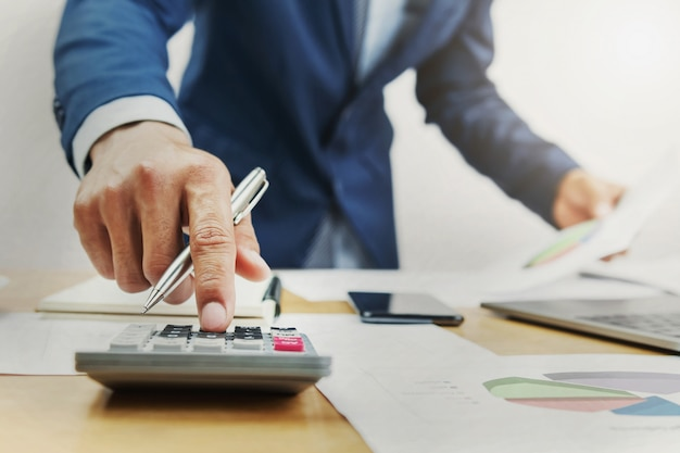 Geschäftsmann, der an schreibtisch arbeitet und taschenrechner im büro verwendet