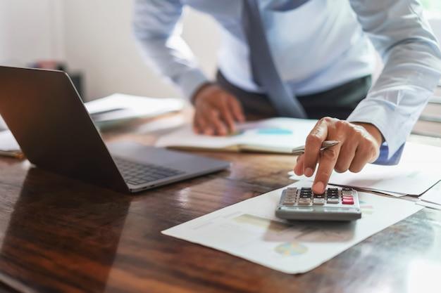 Geschäftsmann, der an schreibtischbüro mit der anwendung eines taschenrechners arbeitet, um geldbericht zu berechnen