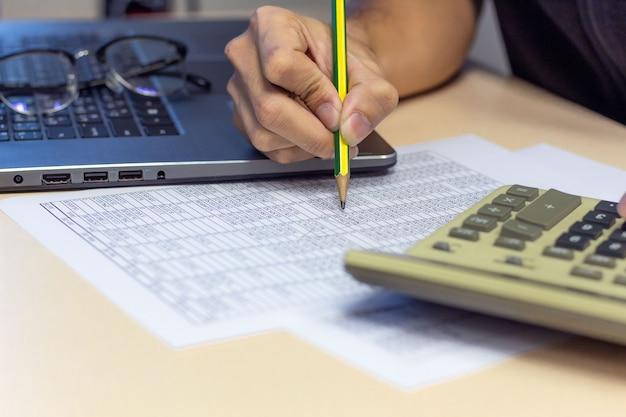 Geschäftsmann, der an schreibtischbüro mit einem taschenrechner- und bleistiftfinanzbericht arbeitet