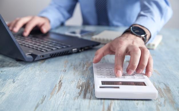 Geschäftsmann, der an seinem laptop arbeitet und taschenrechner benutzt.