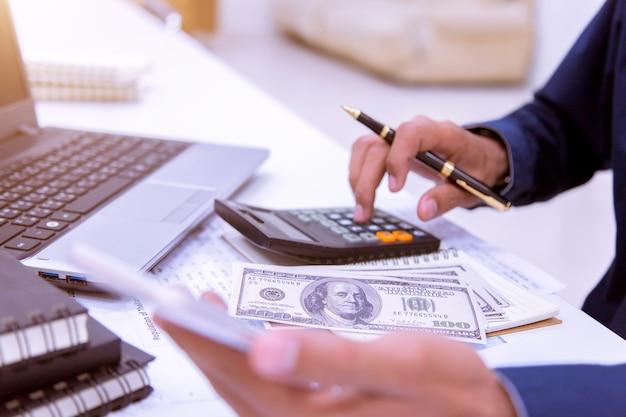 Geschäftsmann, der an seinem schreibtisch im büro mit einem taschenrechner, dokument arbeitet.