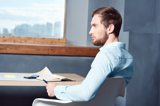 Geschäftsmann, der an seinem schreibtisch im büroleiter sitzt. foto in hoher qualität