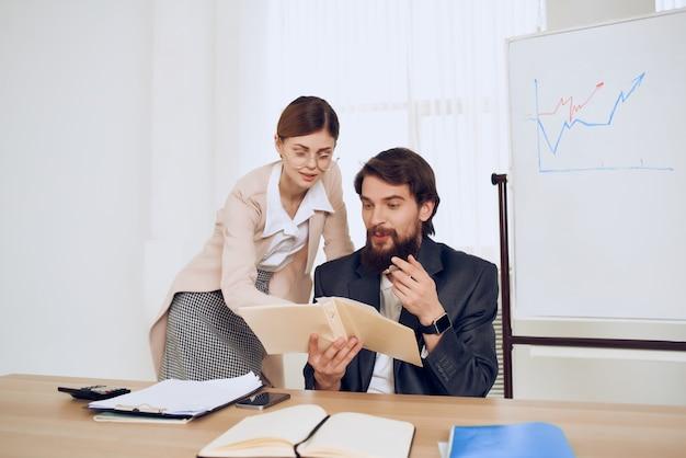 Geschäftsmann, der an seinem schreibtisch neben sekretärarbeitskommunikationsgefühlen sitzt sitting