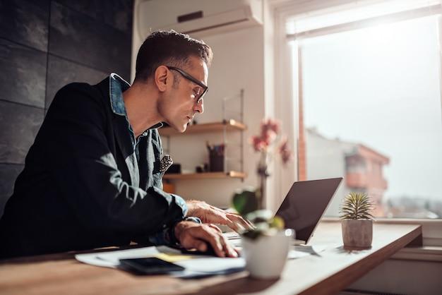 Geschäftsmann, der an seinem schreibtisch sitzt und laptop im büro verwendet