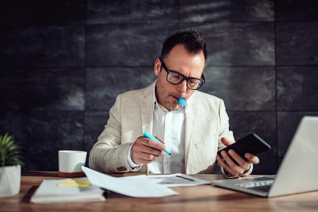 Geschäftsmann, der an seinem schreibtisch sitzt und text hervorhebt