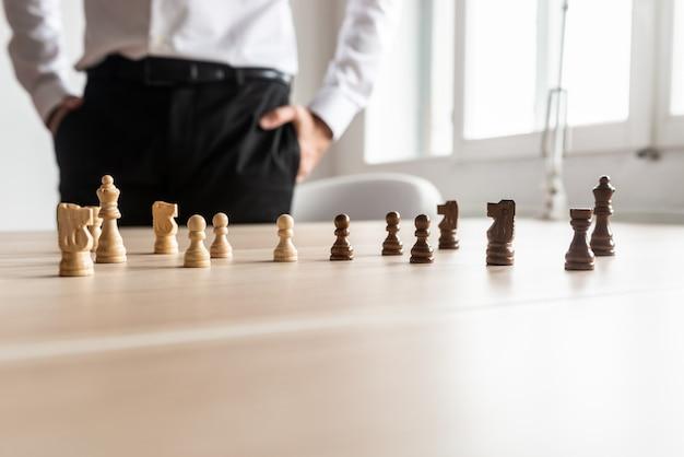 Geschäftsmann, der an seinem schreibtisch steht und auf schwarz-weiße schachfiguren schaut, die auf tdesk angeordnet sind.