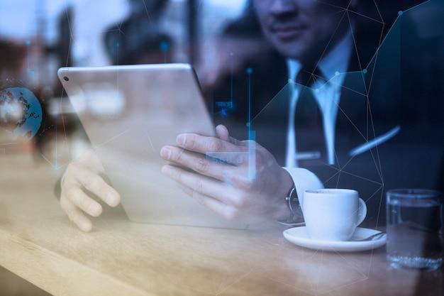 Geschäftsmann, der an tablet im café arbeitet