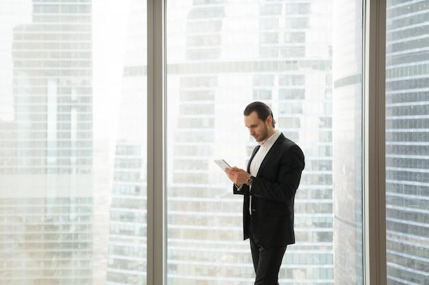 Geschäftsmann, der an tablette nahe großem fenster arbeitet