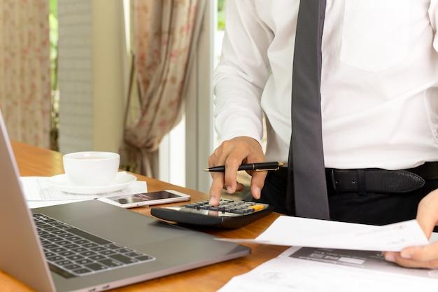 Geschäftsmann, der an taschenrechner arbeitet, um finanzplan zu berechnen