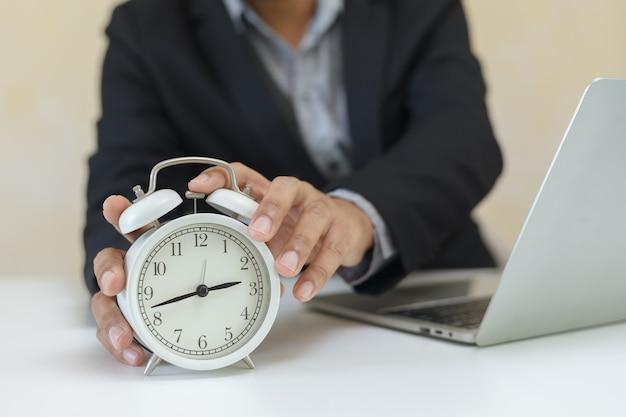 Geschäftsmann, der analogen weißen wecker zum einstellen der zeit am bürotisch hält. arbeitszeitkonzept.
