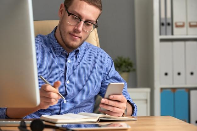 Geschäftsmann, der anzeigen-app am telefon und am tagebuch überprüft