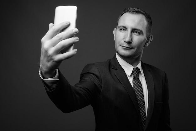 Geschäftsmann, der anzug gegen graue wand in schwarzweiss trägt