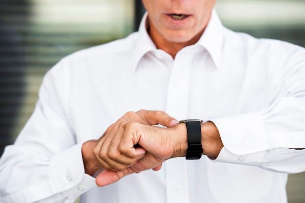 Geschäftsmann, der armbanduhr betrachtet