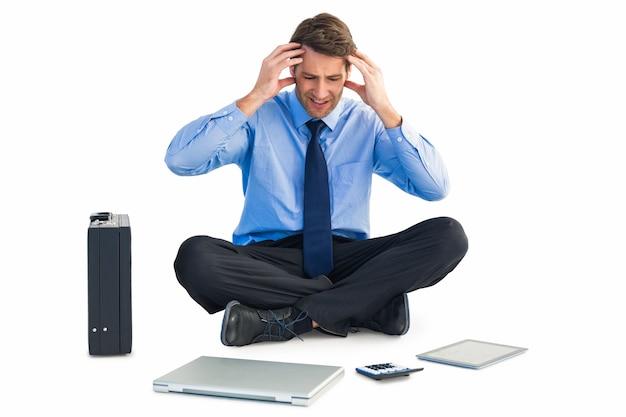 Geschäftsmann, der auf dem boden mit kopfschmerzen sitzt