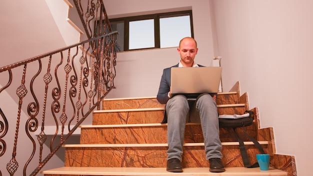 Geschäftsmann, der auf dem laptop tippt und am telefon sitzt, sitzt auf der treppe in der finanzgesellschaft, die jahresberichte überprüft. team von professionellen geschäftsleuten, die im modernen finanzgebäude arbeiten.