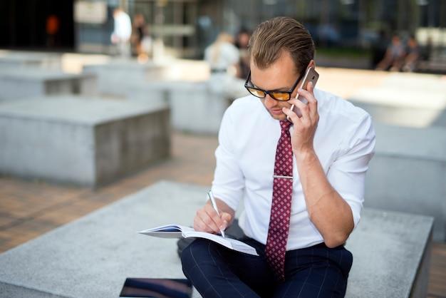 Geschäftsmann, der auf dem mobiltelefon beim schreiben auf seine tagesordnung spricht