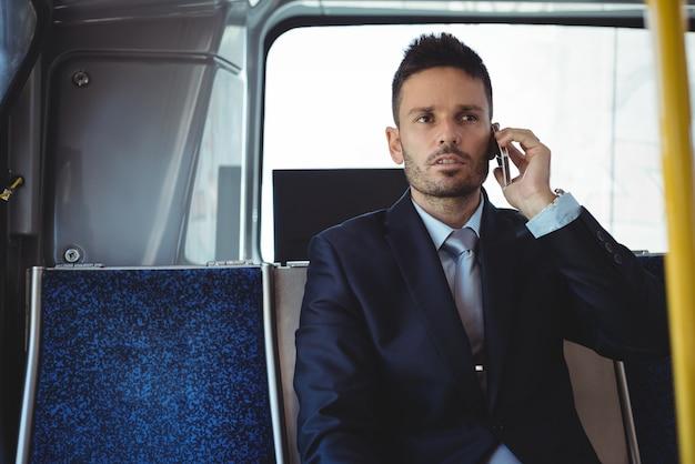 Geschäftsmann, der auf dem mobiltelefon während der reise spricht