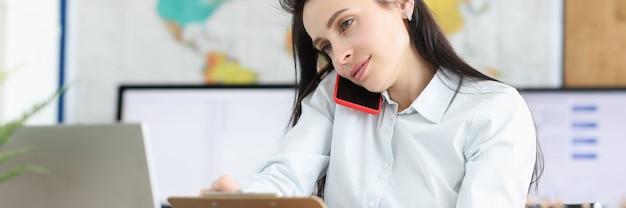 Geschäftsmann, der auf dem smartphone spricht, während er am arbeitsplatz sitzt