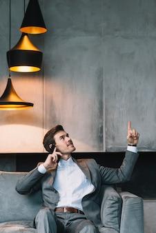 Geschäftsmann, der auf dem sofa spricht durch das mobiltelefon oben schaut sitzt
