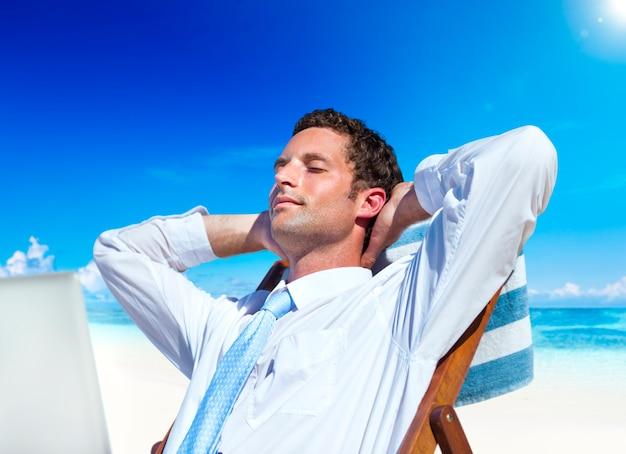 Geschäftsmann, der auf dem strand sich entspannt.