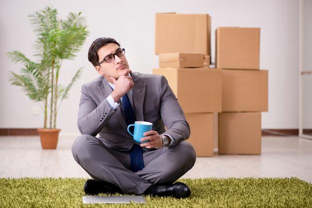 Geschäftsmann, der auf dem teppich im büro sitzt