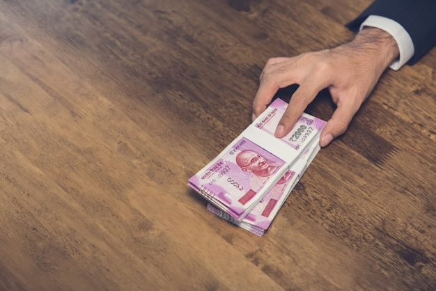 Geschäftsmann, der auf dem tisch stapel geld, währung der indischen rupie gibt (anbietet)