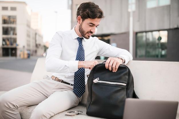 Geschäftsmann, der auf der bank schaut innerhalb seines rucksacks sitzt