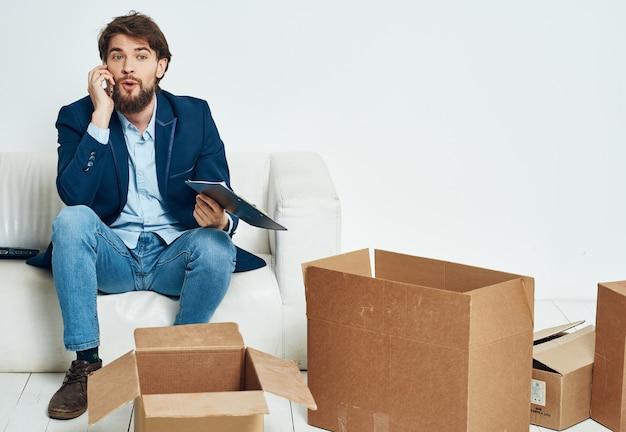 Geschäftsmann, der auf der couch sitzt und auf dem telefonzellenbeamten spricht